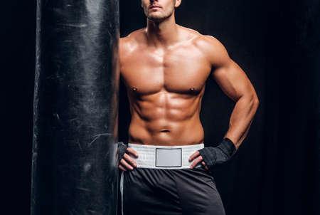 Hombre deportivo atractivo está posando con saco de boxeo en estudio fotográfico oscuro.