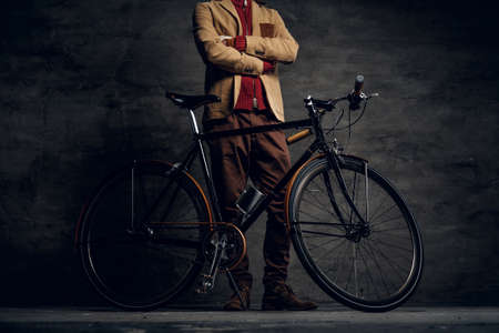 Man with his bicycle is posing for photographer at dark photo studio.