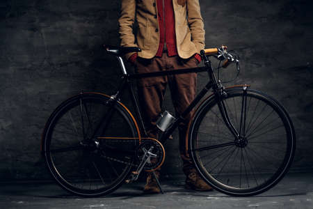 Man with his bicycle is posing for photographer at dark photo studio. Archivio Fotografico