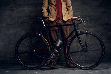 Mann mit seinem Fahrrad posiert für Fotografen im dunklen Fotostudio. Standard-Bild