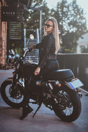 Sexy dramatic woman is parking her shiny new motorbike next to brick wall.