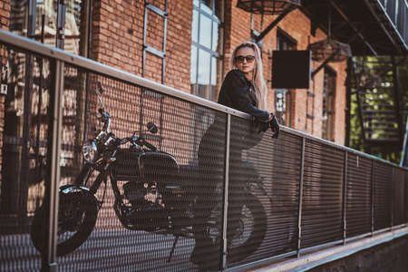 Portrait of mature sexy woman standing on the balcony next to her motorbike. Фото со стока