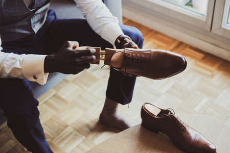 Posh elegant groom is dressing up his leather brown shoes while sitting on sofa.