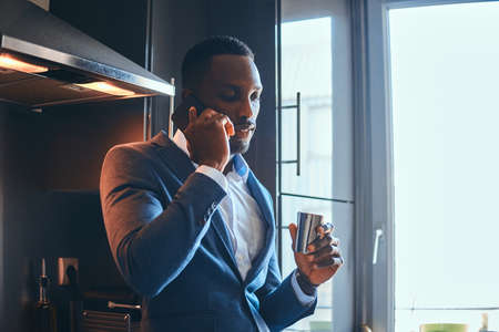 Elegant african man is enjoying his morning coffee while talking by mobile phone at his kitchen. Imagens