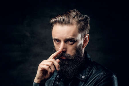 Portrait of hopeless bearded man with hairstyle on the black background.