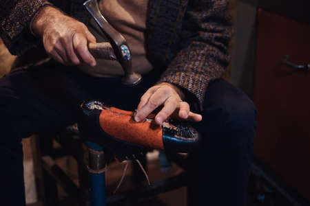 Closeup photoshoot of man making comfortable hand made shoes for people. Stock Photo
