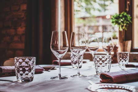 There are glasses for wine and water on the table with white cloth are ready for dining.