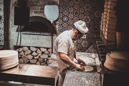 Italian chef in uniform is preparing pastry for pizza at the kitchen. Reklamní fotografie