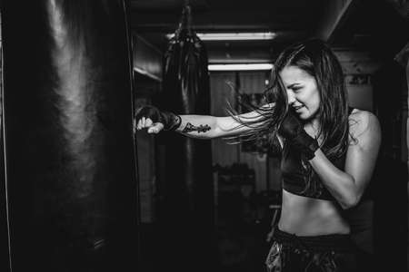 Happy smiling girl has a boxing training at gym with punching bag, black and white photo.