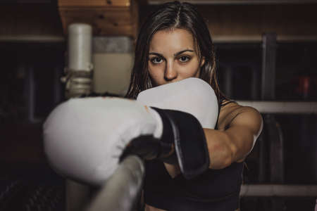 Young slim female boxer is ready to fight while standing at her corner on the ring.