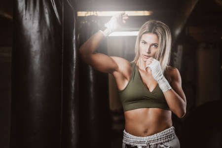 Attractive blond woman has a boxing training with punching bag at kick boxing studio.