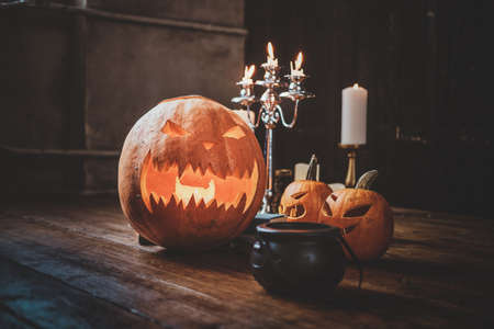 Halloween traditional carved pumpkins, small boiler and candles on the wooden floor.