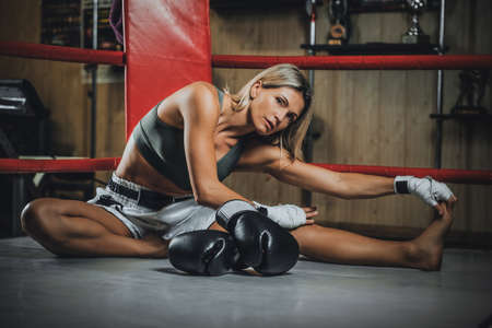 Blonde pretty woman is warming up before sparring while sitting at her corner on the ring.