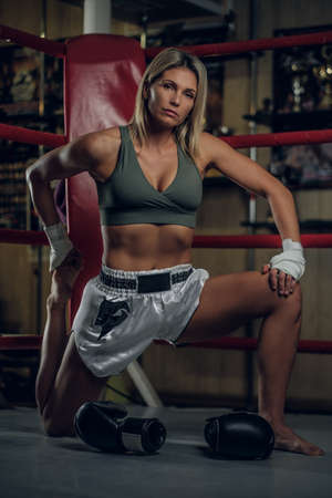 Beautiful fit woman is doing stretching for legs while preparing for sparring.