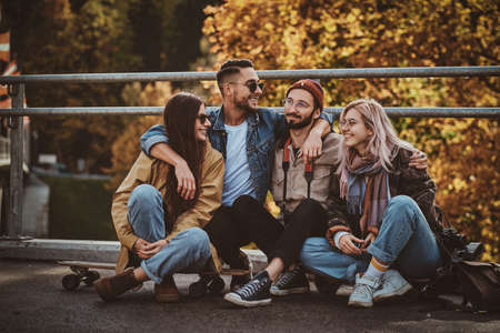 Happy cheerful friends are enjoying autumn walk in the golden leaves park. Stock Photo