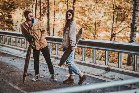 Beautiful romantic couple with longboards are walking in sunny autumn park.