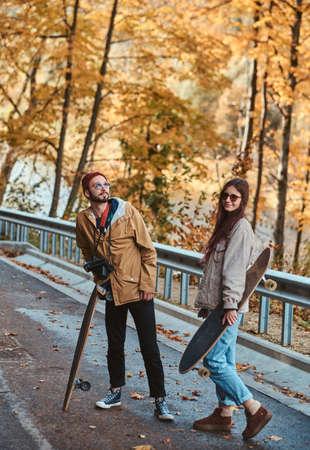 Beautiful romantic couple with longboards are walking in sunny autumn park. 版權商用圖片 - 131803172