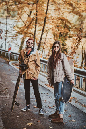 Beautiful romantic couple with longboards are walking in sunny autumn park. 版權商用圖片 - 131803173
