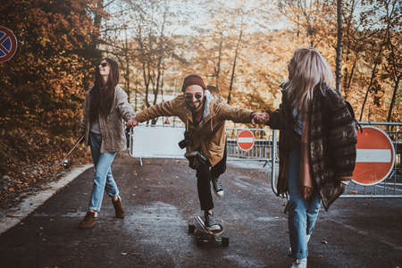 Two young women are teaching their friend how to ride skateboard while walking in autumn park. 版權商用圖片 - 131803175