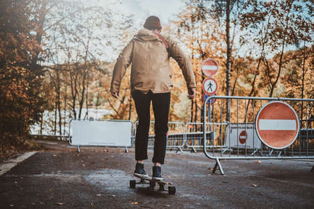 Young trendy man is riding his longboard at autumn park surrounded with yellow trees.