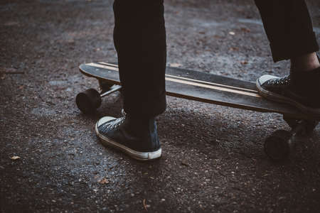 Young hipster is learning how to ride longboard while walking at autumn park. 版權商用圖片 - 131803178