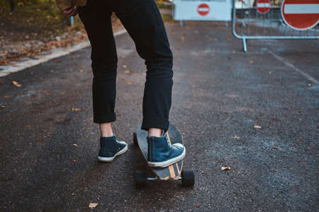 Young hipster is learning how to ride longboard while walking at autumn park. 版權商用圖片 - 131769969