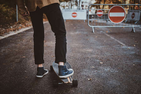 Young hipster is learning how to ride longboard while walking at autumn park. 版權商用圖片 - 131769770