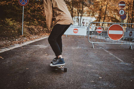 Young trendy man is riding his longboard at autumn park surrounded with yellow trees. 版權商用圖片 - 131769907