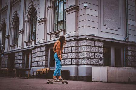 Skater girl in denim is riding her longboard on the street. 版權商用圖片