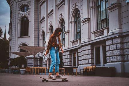Skater girl in denim is riding her longboard on the street. 版權商用圖片 - 131769588