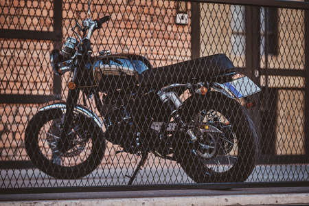 Brand new, shiny black retro chopper is parked next to brick building, behind the fence. Stock Photo