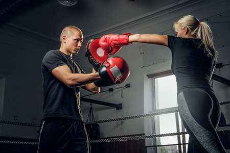 Strong blond woman is trying to attack her coach while have boxing training. Banco de Imagens