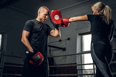 Strong blond woman is trying to attack her coach while have boxing training. Stock Photo