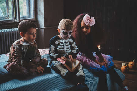 Little friends are waiting for Halloween party while reading book and sitting on bed.