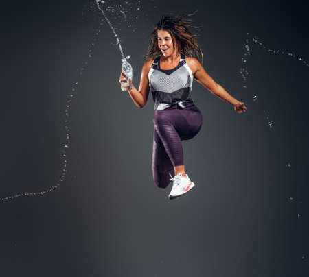 Happy joyful girl is jumping with bottle of water making splashes at photo studio on dark background. Stockfoto