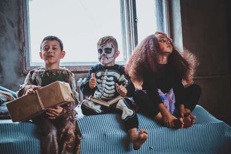 Pensive kids are sitting on the bed wearing Halloween costumes, boy is holding a box. 写真素材 - 131936839