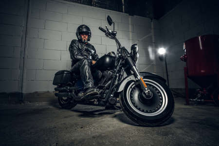 Serious man in helmet and black leather suit is sitting on his motorbike.