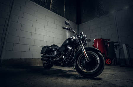 Beautiful shiny bike is parked in dark garage with white walls.