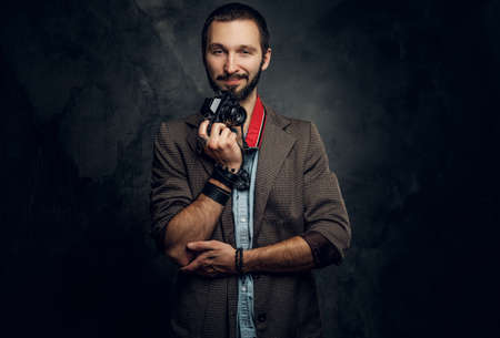 Attractive pensive man with photo camera is posing for photographer at dark photo studio.