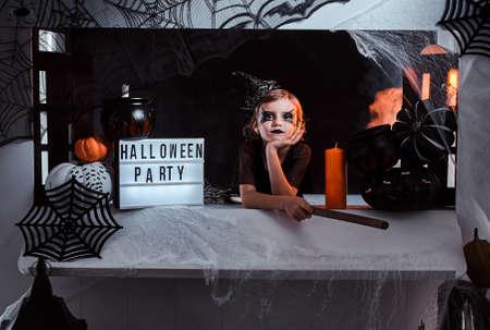 Kleine Hexe lädt ihre Freunde zu einer Party ein, sie sitzt in einem schön dekorierten Raum, es gibt Spinnennetz, Kürbisse und Besen.