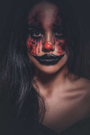 Portrait of young woman in a role of evil scary clown at dark photo studio.