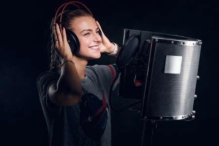 Young pretty singer is recording her new album at recording studio. Stock Photo