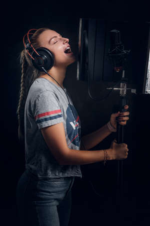Focused emotional girl is singing her new passion song for recording at studio.