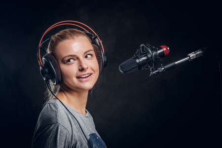 Recording a new song - attractive singer is singing new audio material. Stockfoto