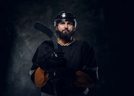 In the dark photo studio brutal experienced hockey player has a photo session.