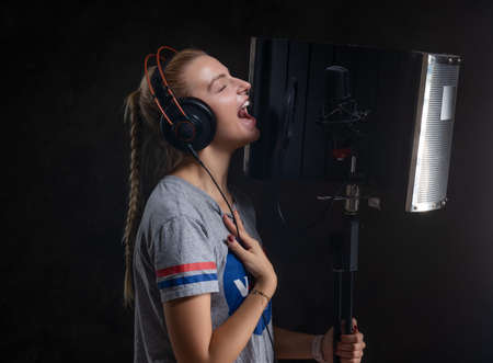 Focused emotional girl is singing her new passion song for recording at studio. Stockfoto