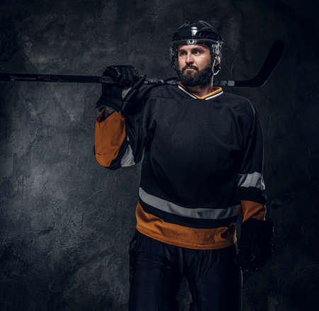 Portrait of brutal bearded man in hockey player uniform at dark photo studio.