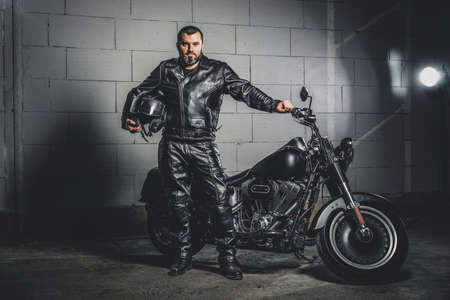 Brutal bearded biker in leather suit is standing next to his bike while holding a helmet.