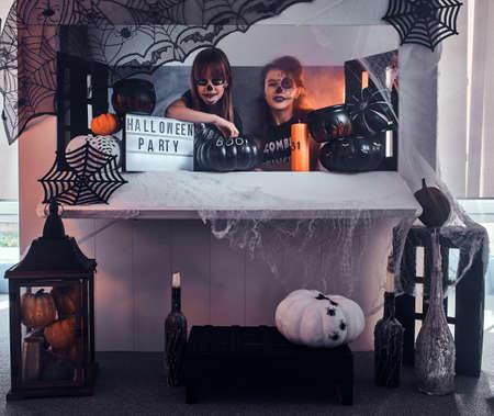Dos chicas pensativas con maquillaje aterrador están sentadas junto a una mesa decorada tradicionalmente. Foto de archivo