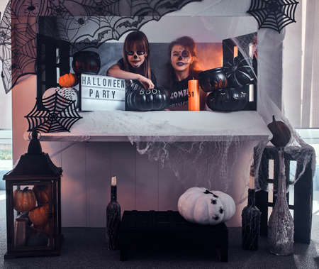 Two pensive girls with scary makeup are sitting next to traditionally decorated table. Banque d'images